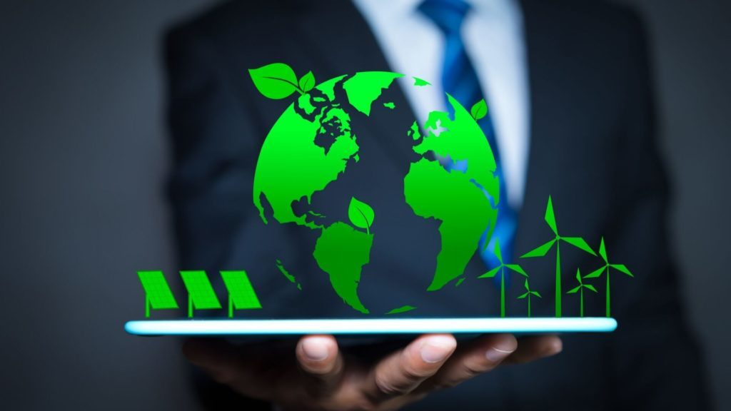 Business Man holding an iPad with a Green Earth and Solar Panels