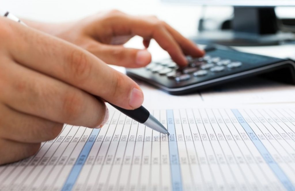 Using a calculator to calculate spreadsheet on desk