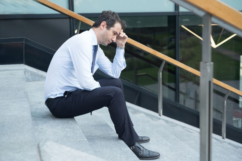 Business Man sitting on outdoor steps looking like he is struggling