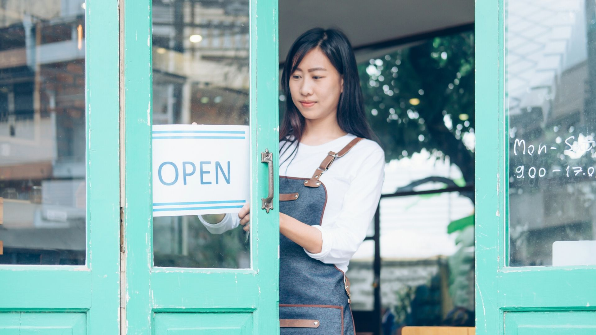 business woman putting an open sign on her shop