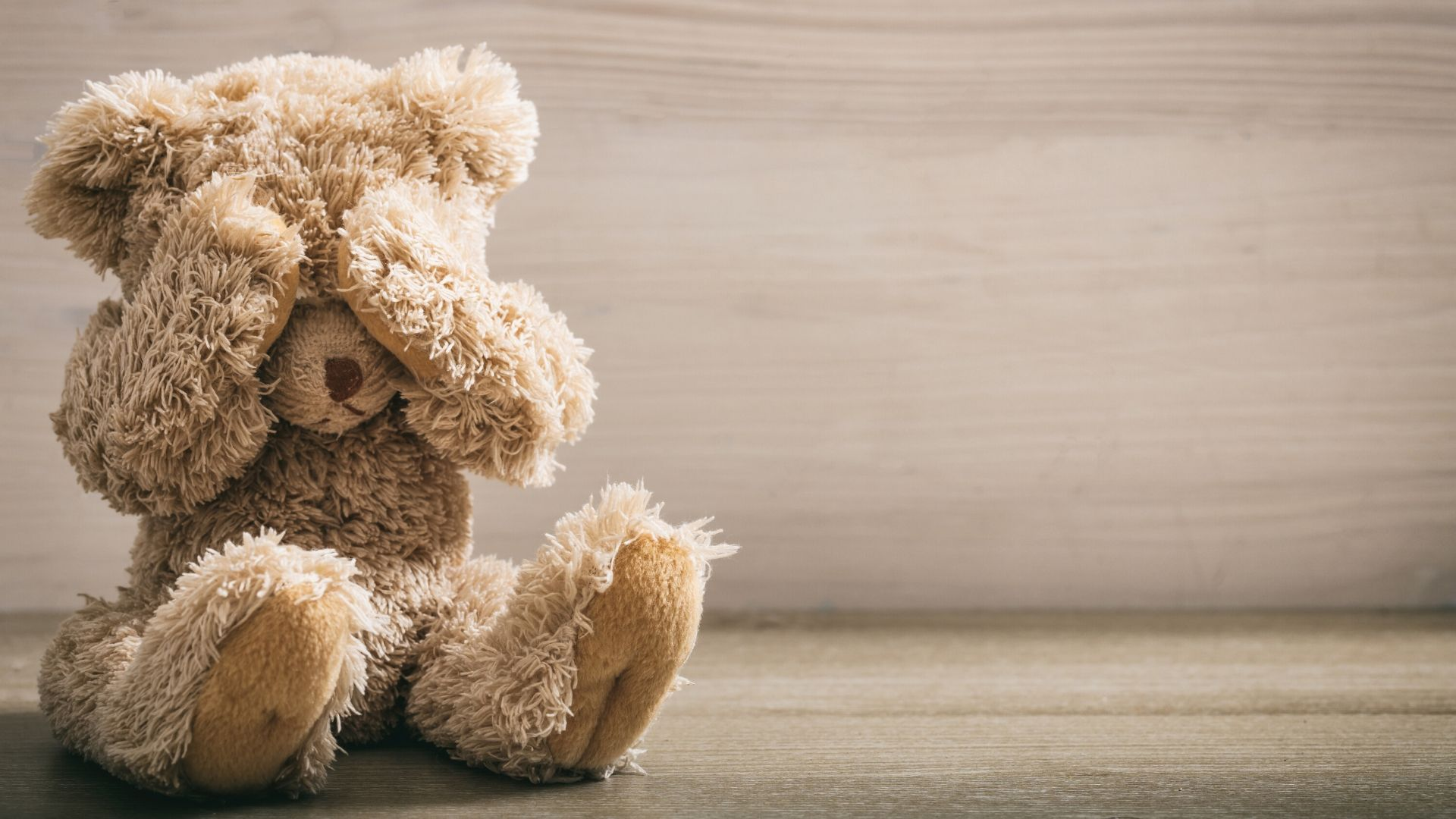 teddy bear with its hands over its eyes