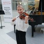 A happy boy playing violin at Musicthon 2018