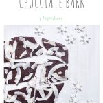 dark chocolate bark sprinkled with coconut and salt with wooden snowflakes scattered next to it