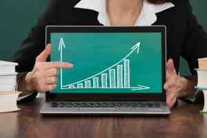 Close-up Of Female Teacher Pointing At Graph On Laptop