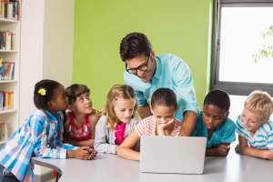 Teacher and kids using laptop in library at school
