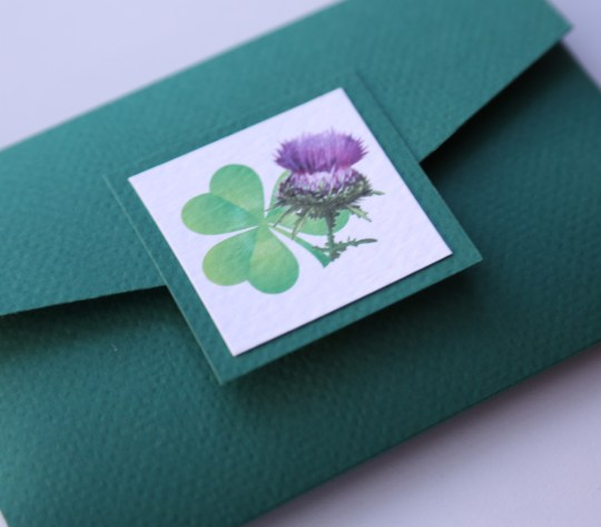 Angelfins, Thistle and Shamrock Pocketfold wedding invitation, The wallet is made from forrest green  card complete with additonal thistle & shamrock  photo embellishment and velcro fasteners  Inside there will be a white  insert attached  containing the details of your event.  In the pocket there will be two card inserts which can contain information for your guests such as RSVP details, maps, accomodation or gift list.