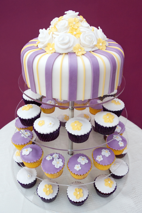 purple_and_yellow_cake_with_cupcakes_underneath_portrait