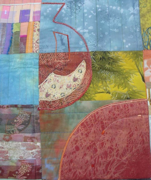 Close up look at the beautiful blend of fabrics, patterns, stitches, and threads in Eleanor's Pomegranates quilt.