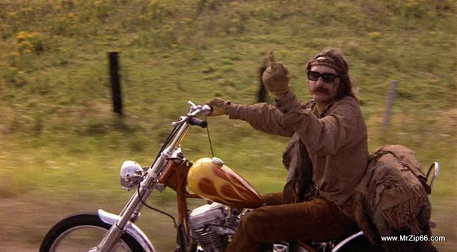 "Picture of Dennis Hopper riding a motorcycle, flipping off the camera- from the movie, ""Easy Rider."""