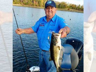 """Lonnie Stanley grabs a big bass that bit his new, reintroduced """"Code-Red"""" VibraWedge spinnerbait."""