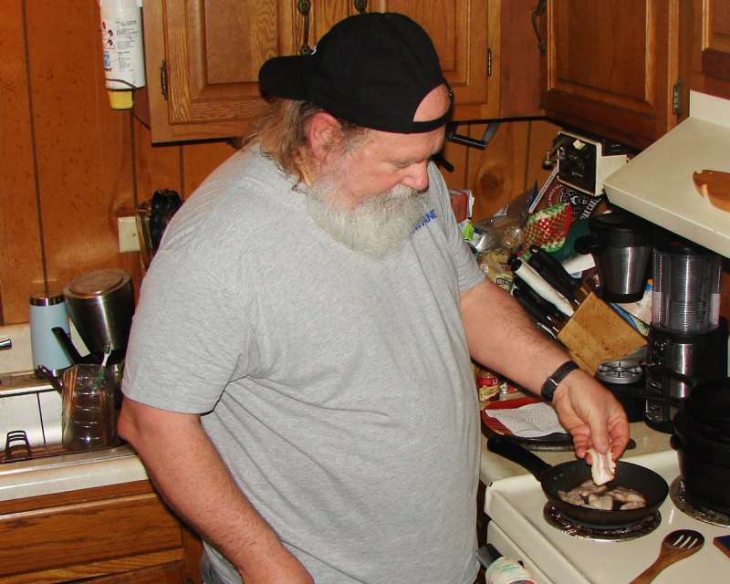 The author cuts bacon as part of the preparation of the relish that accompanies the quail and rice.