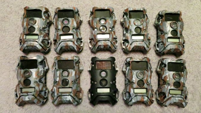 This photo shows 10 trail cameras — nine the author painted himself and one unpainted.