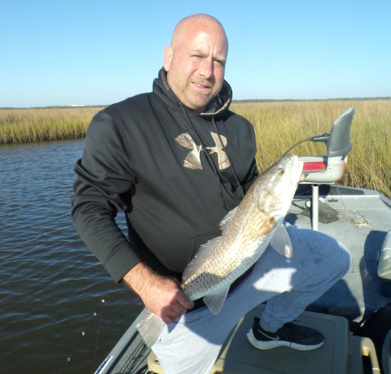 Travis Brashier with a beautiful redfish caught on a Matrix Shad in shallow water near marsh close to Bayou Cumbest. (Photo by Jerry Brashier)