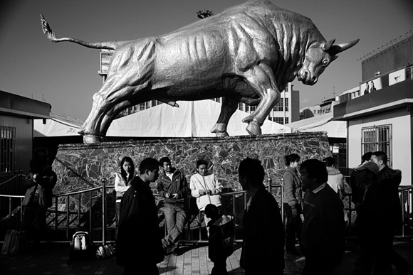Travelers walk past a large bull sculpture outside the Kunming Railway Station in Kunming, Yunnan Province, China.