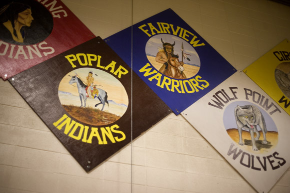 Area school teams' mascots and logos hang in the gym of Harlem High School in Harlem, Montana.