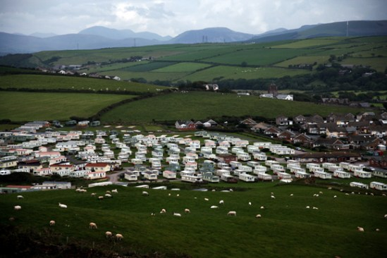 Pastures stretch to the horizon outside of St. Bees, Cumbria, England. In the foreground, sheep graze near a trailer park.