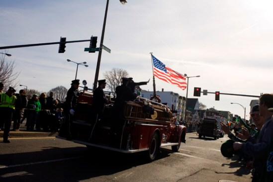 Firefighters ride an engine down Dorchester Street as part of the St. Patrick's Day Parade in South Boston, Massachusetts.