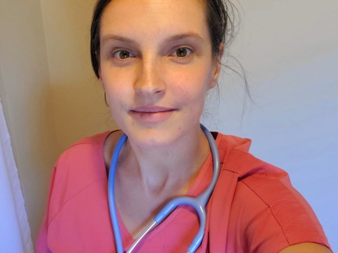 portrait of a white presenting woman with brown eyes and hair in a midwife's scrubs with a stethoscope around her neck