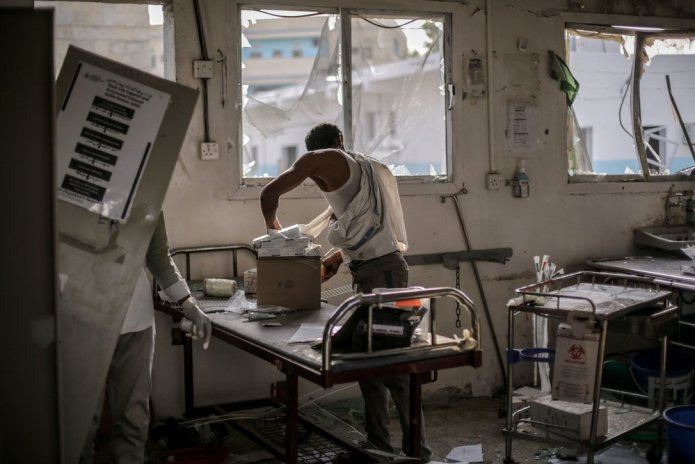 A hospital worker salvages the remains of undamaged medication and equipment left in the emergency room after the 15 August 2016 Saudi-led coalition airstrike which destroyed the hospital killing 19.