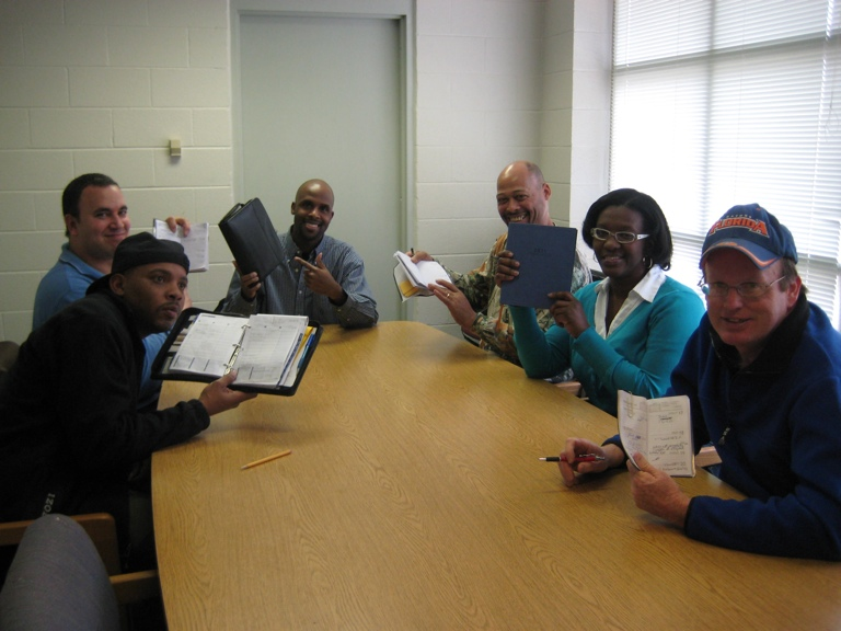 Group around a table holding up notebooks