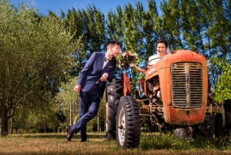 bride on a tractor and groom standing next to her