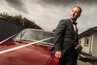 Groom posing by red car