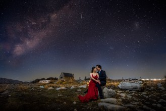 Newlyweds sitting on a boulder bellow milky way