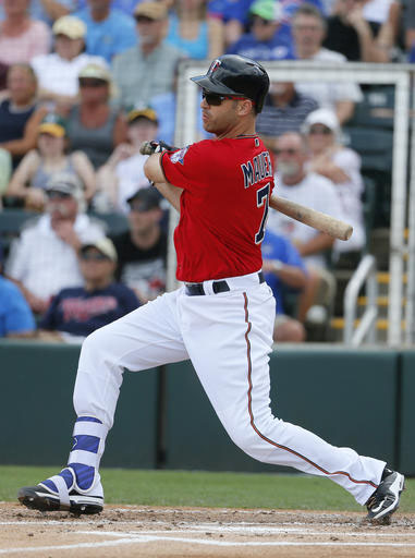 Minnesota Twins' Joe Mauer follows through on a run-scoring single off of Toronto Blue Jays' Ryan Tepera in the first inning of a spring training baseball game, Wednesday, March 30, 2016, in Fort Myers, Fla. The Twins' Brian Dozier scored on the hit. (AP Photo/Tony Gutierrez)