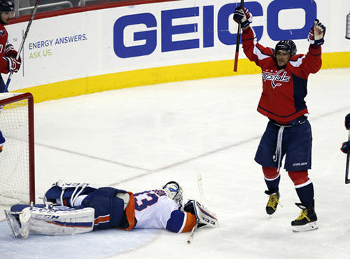 Washington Capitals left wing Alex Ovechkin (8), from Russia, celebrates his goal past New York Islanders goalie Christopher Gibson (33), from Finland, in the third period of an NHL hockey game, Tuesday, April 5, 2016, in Washington. The Islanders won 4-3 in overtime. (AP Photo/Alex Brandon)