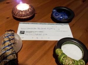 A tax cheque surrounded by representation of the elements.