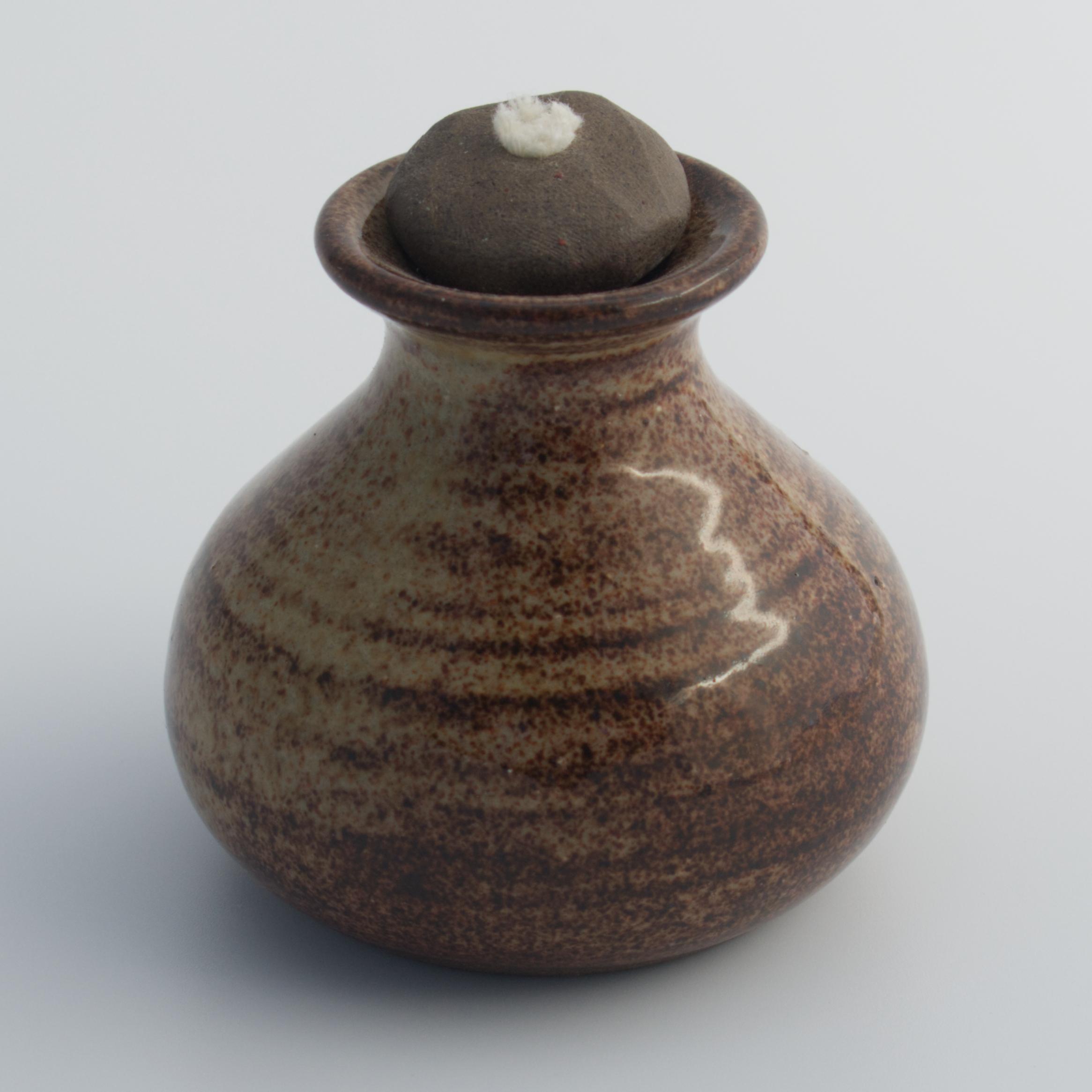 brown ceramic oil lamp