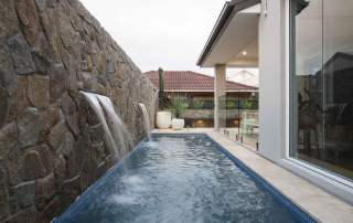Coastal backyard pool with stone wall water feature
