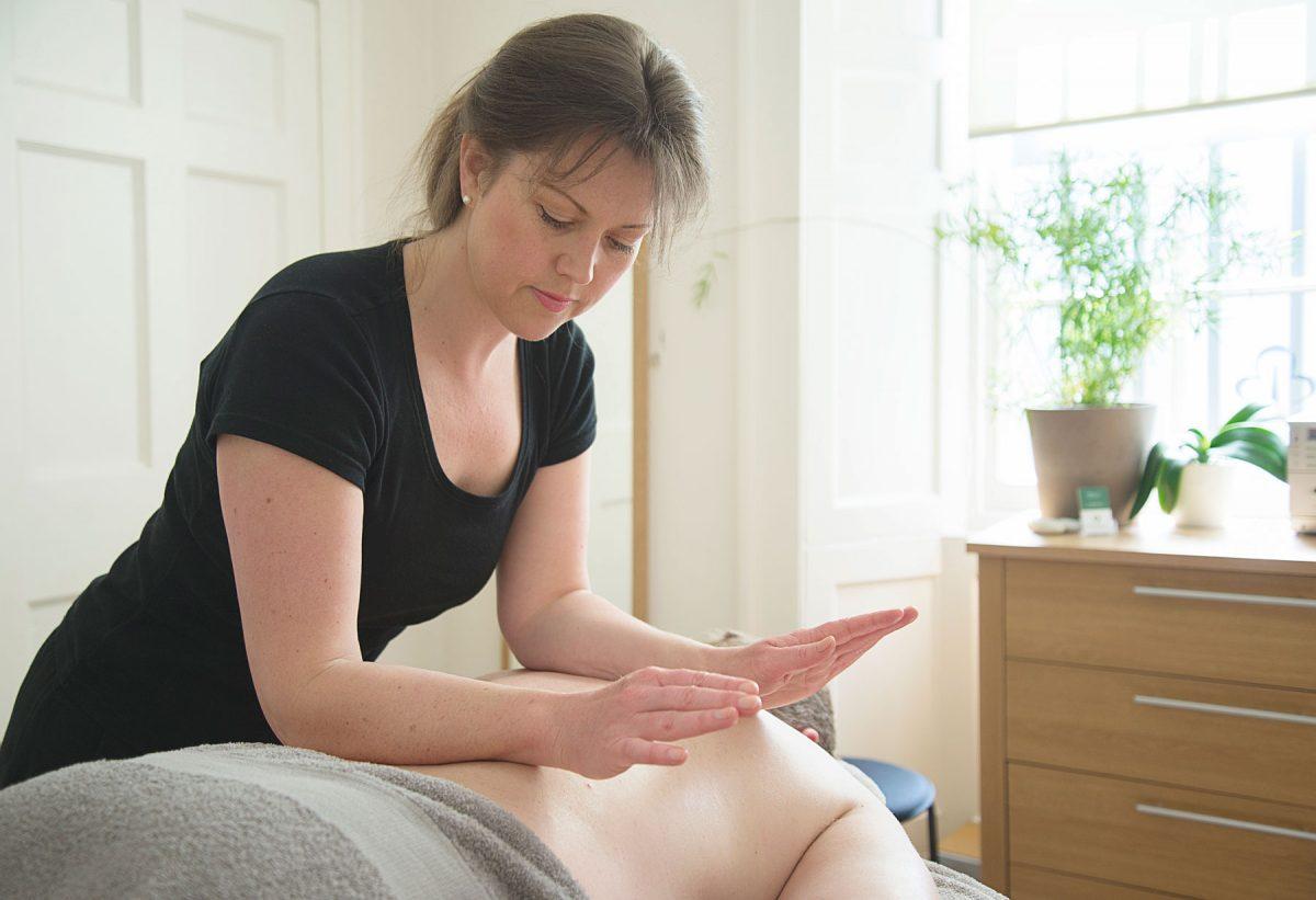 woman massages patients back