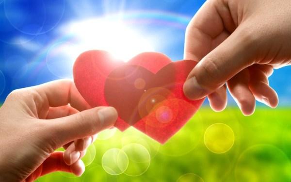 Mãos segurando corações, ao fundo sol e arco-íris.