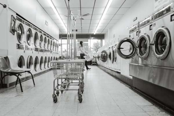 Black and white picture of a woman in a laundry mat