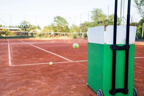 Ball machine on slag tennis court.