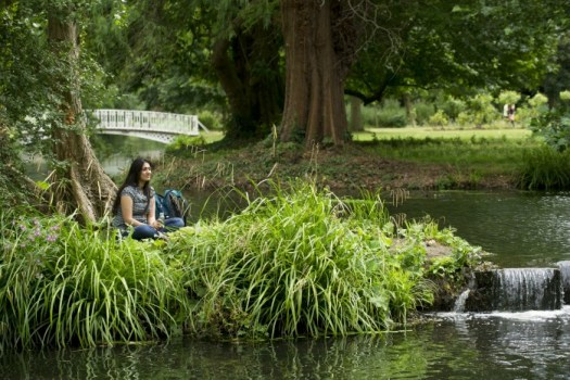 Woman relaxing beside the River Wandle at Morden Hall Park, London. ©National Trust Images John Millar