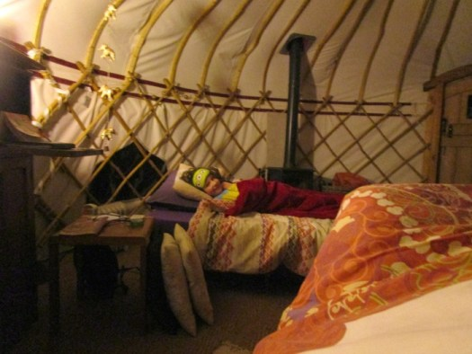 H on her futon in the yurt