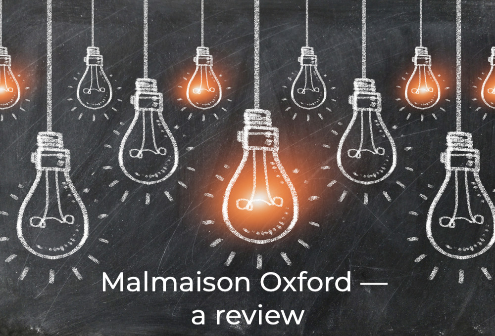A chalk board with lightbulbs drawn in chalk and the words Malmaison Oxford written underneath