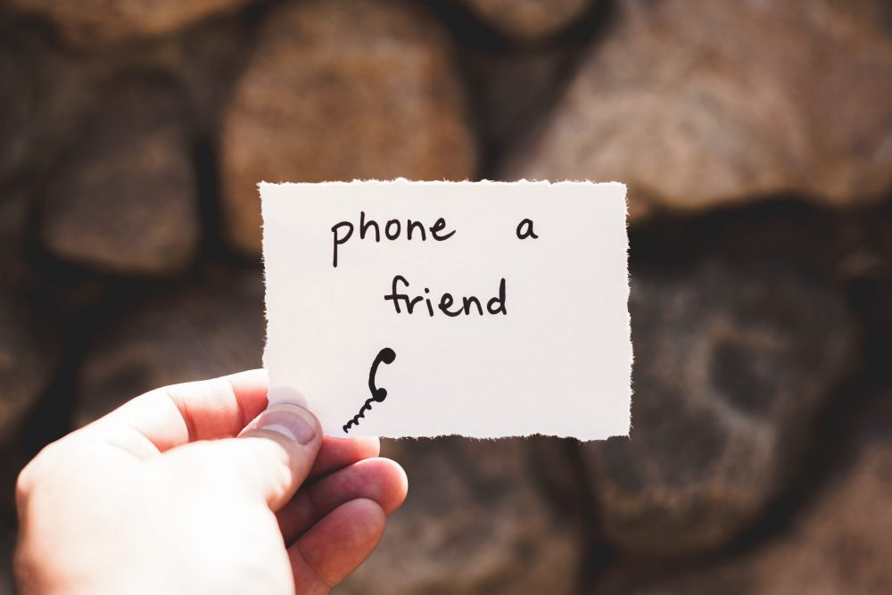 A hand holds a small piece of paper saying the words phone a friend