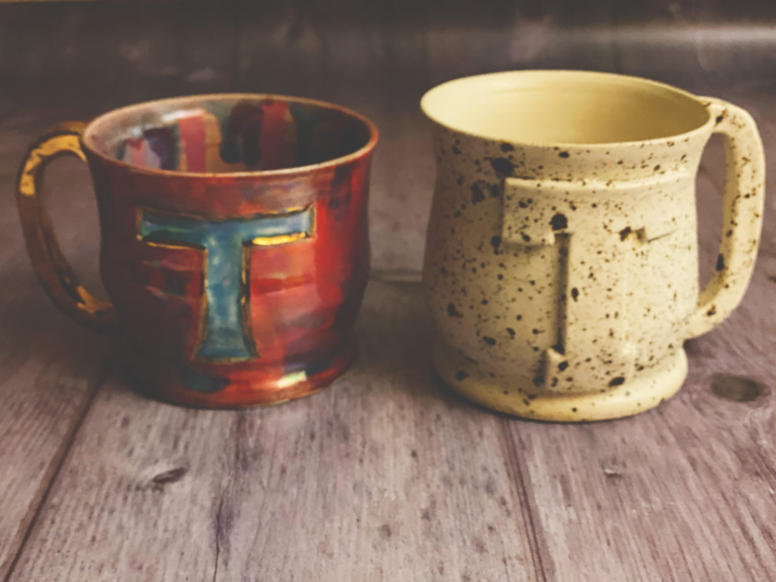 Two hand made mugs, one is cream and one is red but both have the letter T on the front