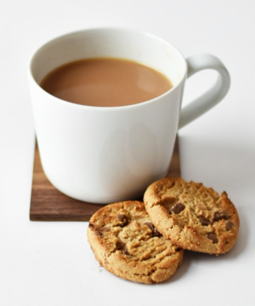 A white mug containing tea with two chocolate chip cookies sit in front