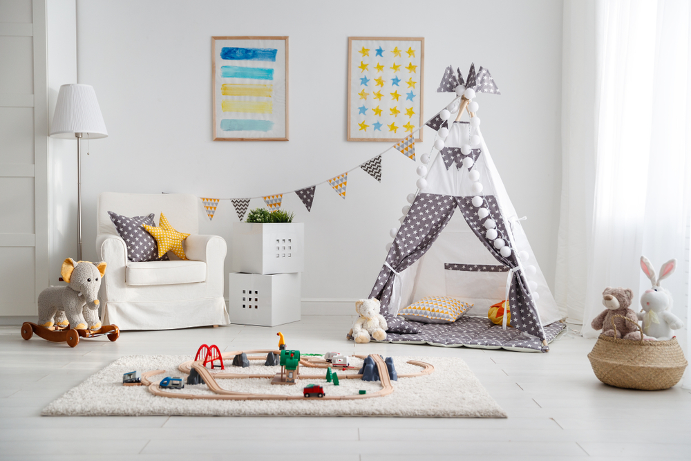 A white bedroom, with a white rug that has a wooden train set on it. In the background is a white tee pee, a white arm chair and lots of children's toys