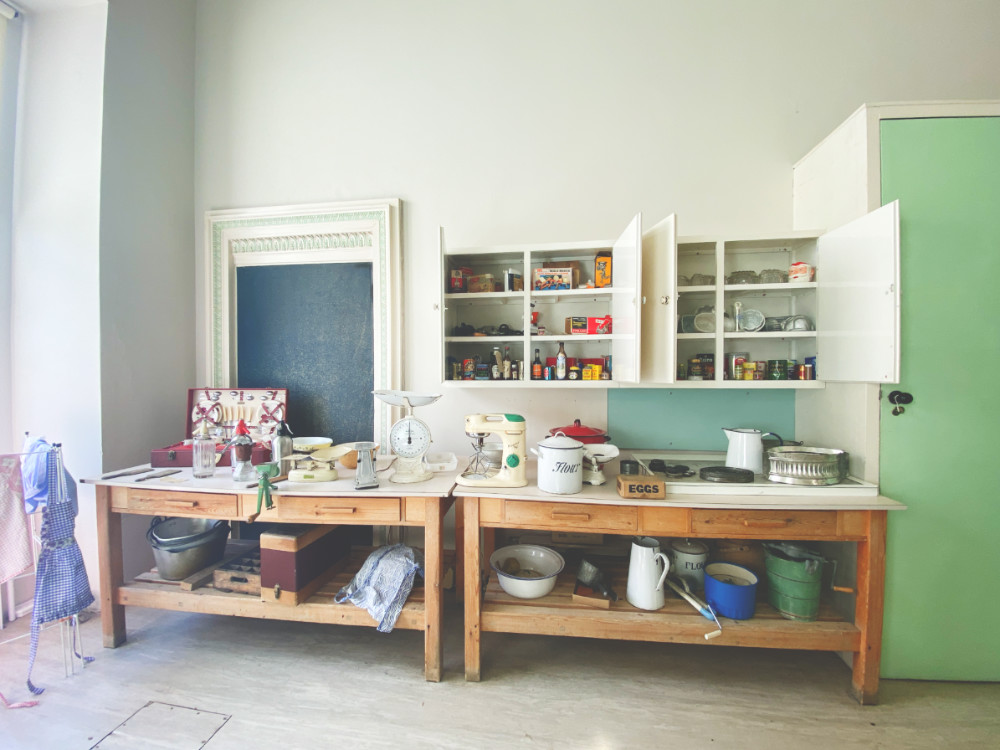 Two counter tops in a 1950s kitchen with cupboards full of 1950s products. There are enamelled tins and containers on the worktop