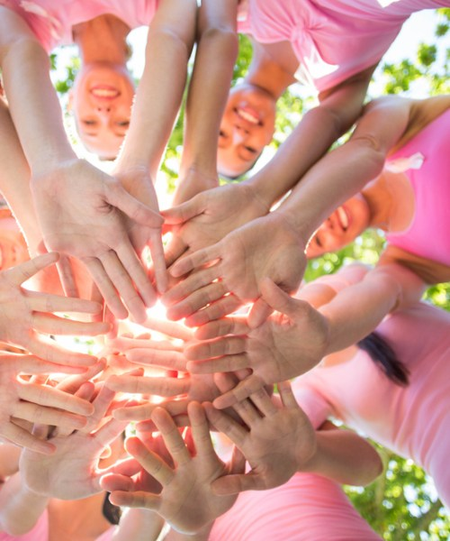 A group of women all wearing pink t shirts are putting their hands together, photographed from underneath