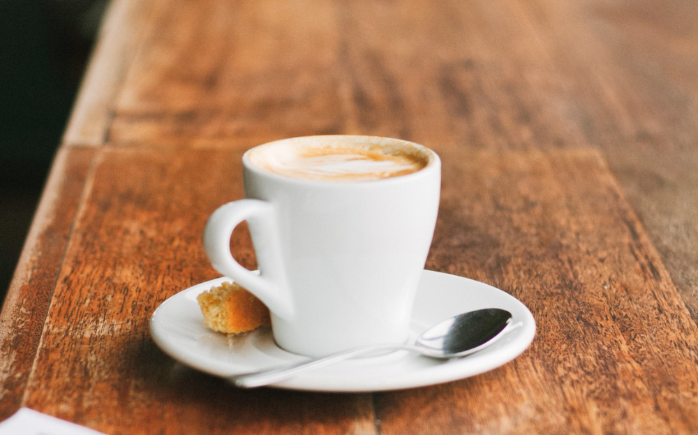 A cup of cappuccino with a white saucer on a wooden counter top