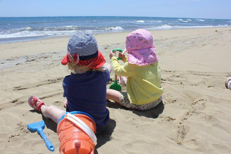 Two girls sitting on the beach at Maspalomas, Gran Canaria