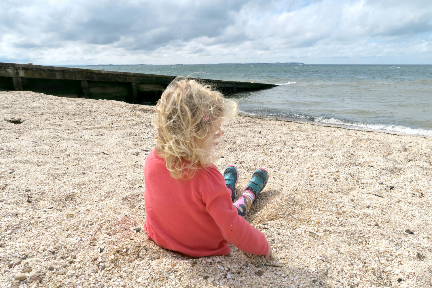 Girl relaxing on the shingle beach at Whitstable looking out to the sea on the Kent coast - my tips from our trip for Whitstable with kids