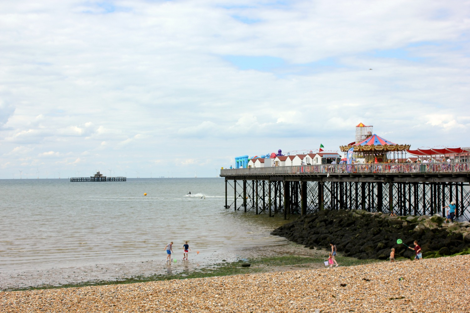 The view of the pier at Herne Bay in Kent on a summer day, with the funfair and classic carousel and people paddling