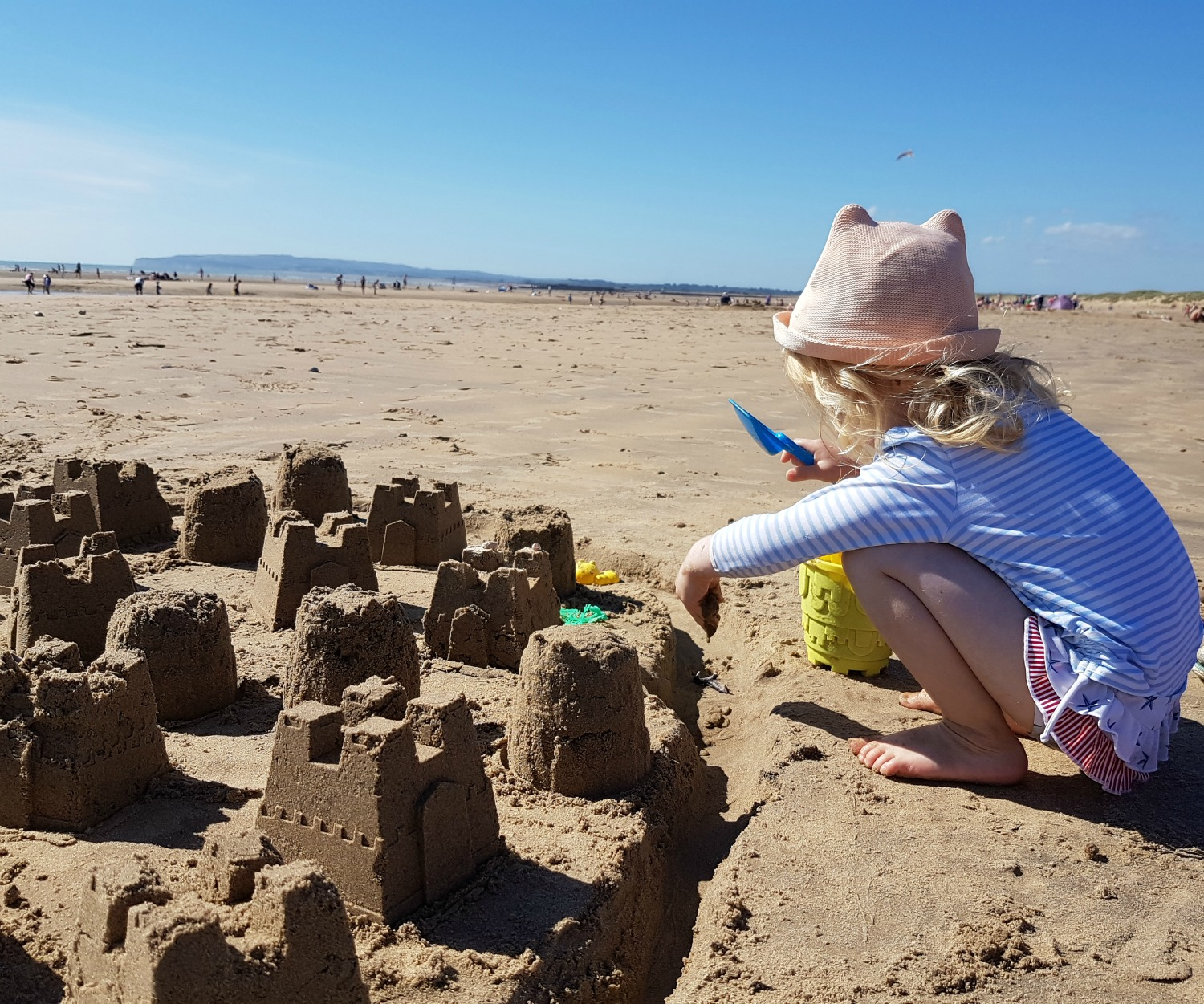 Girl making sandcastles on Camber Sands beach in East Sussex - spending a weekend in East Sussex with my daughter before the start of school, to explore the history and coastline